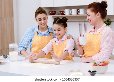 three generations of happy women rolling dough for cookies together at kitchen