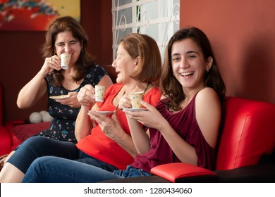 Three generations of hispanic women laughing and drinking coffee at home