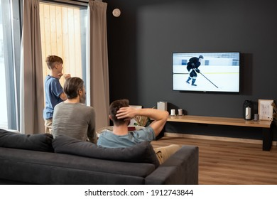 Three generations of men looking at screen of tv set during broadcast of hockey match while sitting in living-room at leisure or weekend