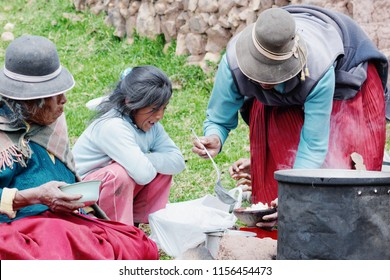 Three generations of native american women eating in the countryside. Aymara culture.