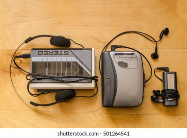 Three generations of portable players: 80s, 90s and 2000s (wooden background)