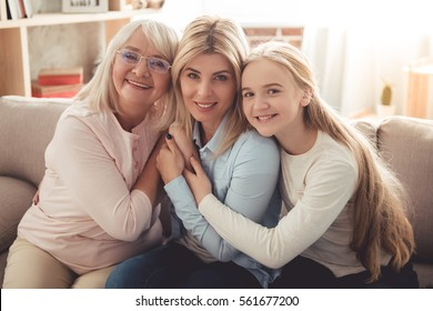 Three generations of women. Beautiful granny, mother and daughter are hugging, looking at camera and smiling while sitting on couch at home