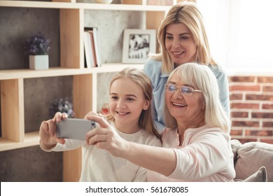 Three generations of women. Beautiful granny, mother and daughter are doing selfie and smiling while sitting on couch at home