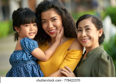 Three generations of women: joyful senior woman looking at camera with toothy smile while posing for photography with her attractive middle-aged daughter and cute little granddaughter