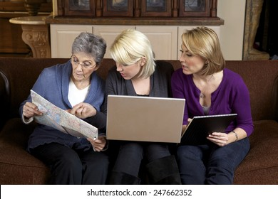 Three generations of women planning a trip with a laptop computer, a map and a notepad