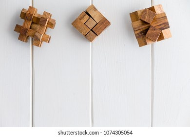 Three geometric interlocked wooden puzzles arranged in a neat line as a top border on white painted wood boards with copy space