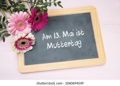 three gerbera flowers on a writing chalkboard, german text Am 13. Mai ist Muttertag, meaning Mai 13 is Mother's Day, bright pink background top view from above, selected focus