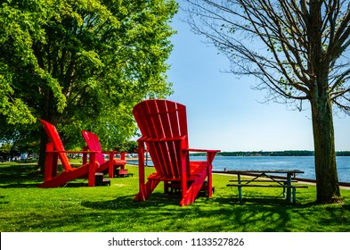 Three giant red adirondack chairs at Brockville overlooking the Thousand Islands, and St. Lawrence River