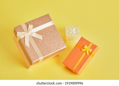 three gift boxes of different colors, sizes and shapes on a yellow background, pink, yellow and orange gift boxes top view