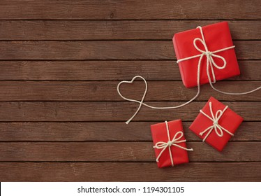 Three gift boxes on the wooden table are wrapped in red paper.