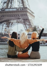 Three girlfriends a brunette, a blonde and a redhead are sitting on the Seine embankment with balloons against the backdrop of the Eiffel Tower. Bachelorette party in Paris.