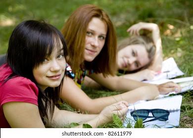 Three girlfriends doing homework at the park.