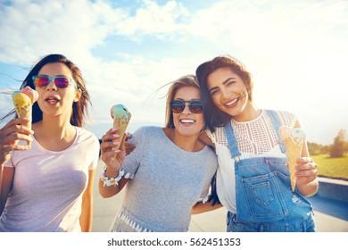 Three girlfriends enjoying a summer treat walking arm in arm on a promenade eating colorful Italian ice cream in cones