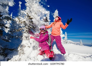 Three girlfriends have fun and enjoy fresh snow on a beautiful winter day in the mountains. Concept friendship