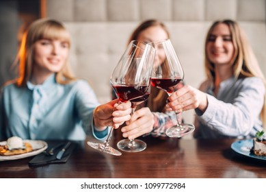 Three girlfriends holding beverages in glasses