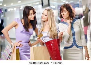 Three girlfriends in shop with bags and a credit card