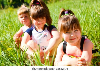 Three girls  with backpacks sitting in grass