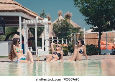 Three girls, best girlfriends hang out at the pool bar hotel and talk about travel summer vacation holiday list and drinking cocktails, wearing sunglasses. Amazing resort water island green beach bar