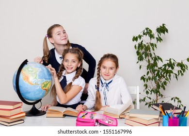 three girls with books and a globe in geography class at the desk