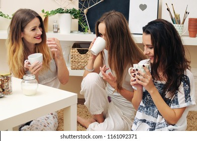 Three girls drink tea and talk