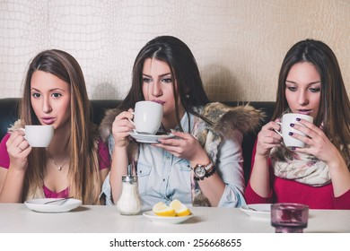 Three girls drinking hot beverage