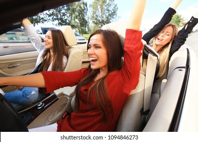 three girls driving in a convertible car and having fun
