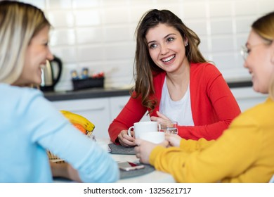 Three girls enjoy talking while drinking coffee in the morning at home.