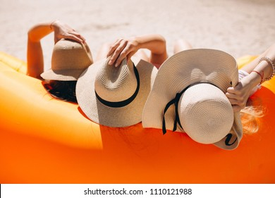 Three girls in hats from the back at the beach