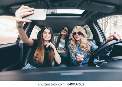Three girls having fun in the car and taking selfies with camera
