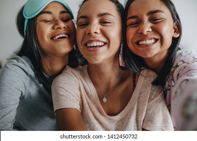 Three girls having fun laughing and posing for selfie. Young girls having fun smiling for a selfie during a sleepover.
