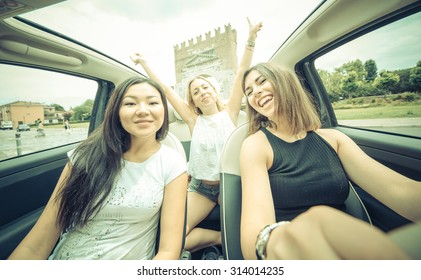 three girls having fun while driving the car. focus on the driver face. concept about transportation and people