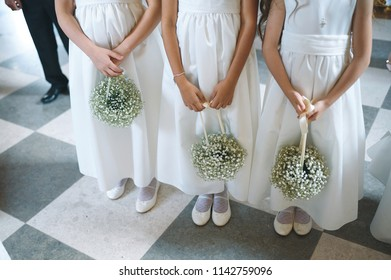 three girls holding bouquets at wedding ceremony