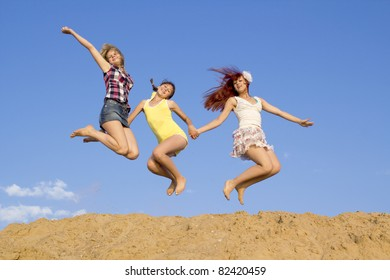 Three girls jump above sand embankment against blue sky