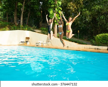 Three girls jumping in swimming pool. Summer vacation.