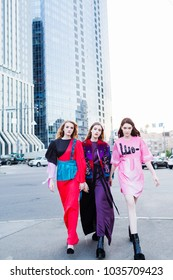 Three girls with long hair in fashionable creative colored dresses are posing on the street, walking  near the business center