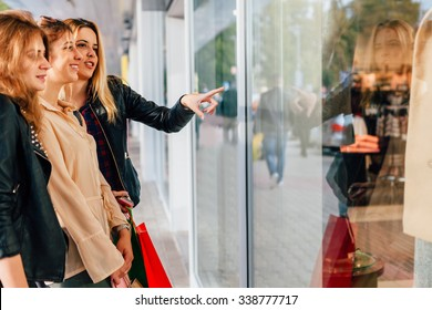 Three girls looking at clothes in a shop window