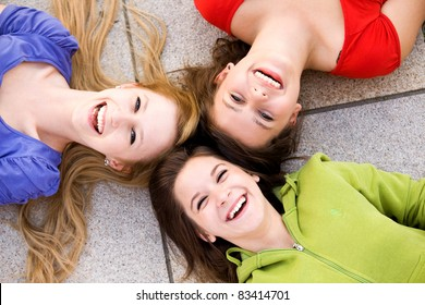Three girls lying in circle