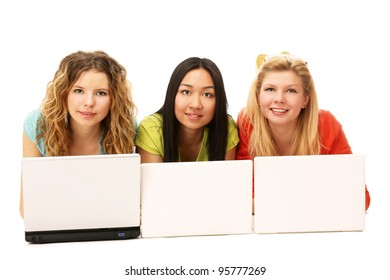 Three girls lying on the floor with a laptop. isolated on white background