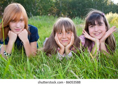 Three girls lying on meadow green grass smiling at camera