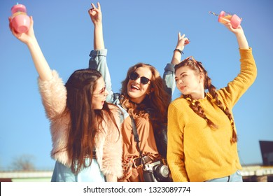 =)Three girls near the river against the sky having fun. Fashion girls in sunglasses. Jump, rejoice, drink drinks, smile have fun, going crazy. Color dressed friends spend SUMMER vibes, time together.