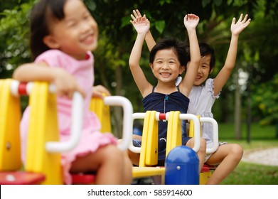 Three girls on a seesaw, arms outstretched