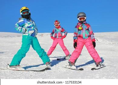 Three girls on the snow with ski equipment