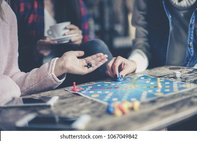 Three girls play together a social game. Focus on hand.
