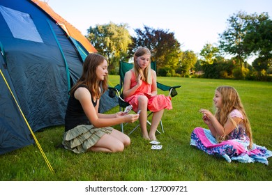 three girls playing card beside their camping tent
