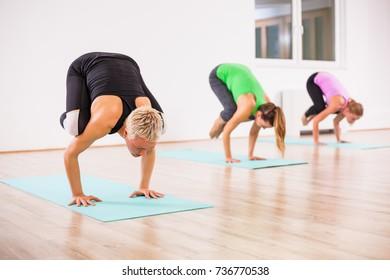 Three girls practicing yoga, Bakasana / Crane pose