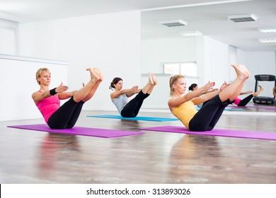 Three girls practicing yoga, Yoga - Navasana / Boat Pose