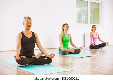 Three girls practicing yoga, Padmasana / Lotus Position