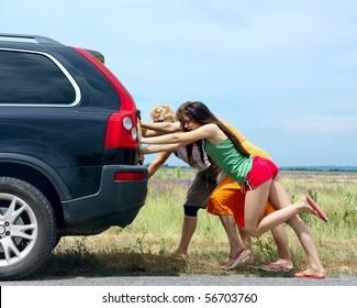 three girls push the broken car