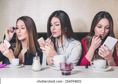 Three girls putting on makeup in a cafe