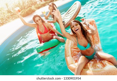 Three girls relaxing and having fun in the pool